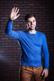 Cute guy waves his hand in greeting Royalty Free Stock Photography