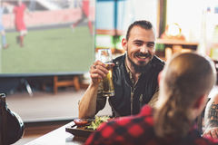 Cute guys enjoying light beer after work. Positive atmosphere. Pleasant handsome men clinking with his friends and smiling. They resting in pub while watching stock photography