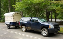A cute hand-built camper hitched to a car. A cleverly constructed little home on wheels as seen at a campground in the summertime Royalty Free Stock Photography