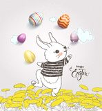 Cute hand drawn bunny dressed in striped t-shirt juggling with colorful eggs on dandelion field and Happy Easter. Handwritten wish against pink background with Royalty Free Stock Photography