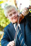 Cute handicapped boy playing violin. Royalty Free Stock Image