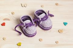 Baby Booties Crochet on wooden background. Of Cute Handmade Baby Booties Crochet on wooden background with wooden buttons Stock Images