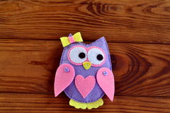 Cute handmade felt owl with bow and heart  on a brown wooden background Stock Image
