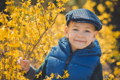 Cute handsome boy in stylish blue dress and hat close to yellow flowers enjoying spring time Stock Photo