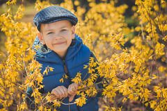 Cute handsome boy in stylish blue dress and hat close to yellow flowers enjoying spring time Royalty Free Stock Photos