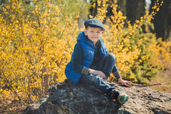 Cute handsome boy in stylish blue dress and hat close to yellow flowers enjoying spring time Royalty Free Stock Images