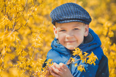 Cute handsome boy in stylish blue dress and hat close to yellow flowers enjoying spring time Stock Photography