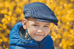 Cute handsome boy in stylish blue dress and hat close to yellow flowers enjoying spring time Royalty Free Stock Photo