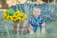 Cute handsome boy wearing jeans close to basket with sunflowers and stones. Stock Photos