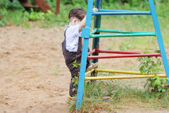 Cute handsome little boy in brown suit climbs up Stock Photography