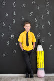 Cute handsome school boy in yellow t-shirt tie and stylish boots casuals standing cloase to black board with numbers and holding h Royalty Free Stock Image