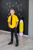 Cute handsome school boy in yellow t-shirt tie and stylish boots casuals standing cloase to black board with numbers and holding h Royalty Free Stock Images