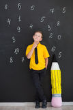 Cute handsome school boy in yellow t-shirt tie and stylish boots casuals standing cloase to black board with numbers and holding h Royalty Free Stock Photo