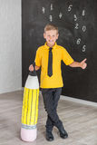 Cute handsome school boy in yellow t-shirt tie and stylish boots casuals standing cloase to black board with numbers and holding h Stock Photography