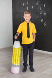 Cute handsome school boy in yellow t-shirt tie and stylish boots casuals standing cloase to black board with numbers and holding h Stock Images