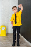 Cute handsome school boy in yellow t-shirt tie and stylish boots casuals standing cloase to black board with numbers and holding s Stock Images