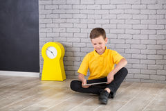 Cute handsome school boy in yellow t-shirt tie and stylish boots casuals standing cloase to black board with numbers and holding t Royalty Free Stock Photography