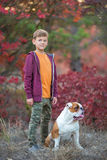 Cute handsome stylish boy enjoying colourful autumn park with his best friend red and white english bull dog.Delightfull. Scene of pretty boy together with Stock Photography