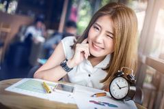 Cute happy asia girl blink eye. Working in coffeeshop with paper graph on wooden table with light flare effect royalty free stock photos