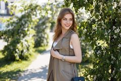 Cute happy attractive young woman in a stylish summer vest in a white T-shirt with a black leather handbag posing in a park. Near the green flowering trees royalty free stock photos