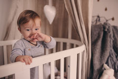 Cute happy baby boy awake in his bed in the morning and playing. Candid capture in real life interior Stock Images