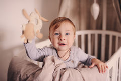 Cute happy baby boy awake in his bed in the morning and playing. Candid capture in real life interior Stock Photo