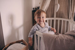 Cute happy baby boy awake in his bed in the morning and playing. Candid capture in real life interior Royalty Free Stock Images