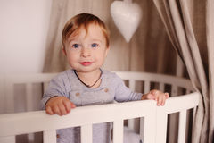 Cute happy baby boy awake in his bed in the morning and playing. Candid capture in real life interior. Cute happy baby boy awake in his bed in the morning and Stock Photo
