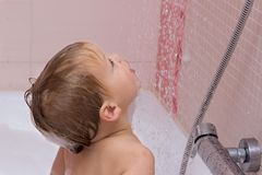 Cute happy baby boy with blonde curly hair in shower standing under water jet in the bath royalty free stock photography