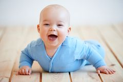 Cute happy baby boy crawling on the floor Stock Photo