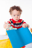 Cute happy baby boy cutting colorful paper Royalty Free Stock Photography