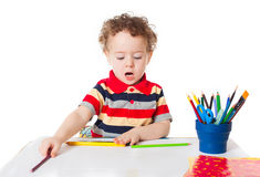 Cute happy baby boy drawing with pencil. Cute happy baby boy kid child playing and drawing writing and talking, isolated on white background studio portrait Royalty Free Stock Photo