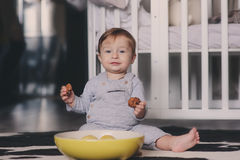 Cute happy baby boy eating cookies at home and playing with plate of lemons. Lifestyle indoor capture Royalty Free Stock Photography