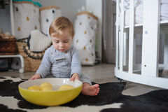 Cute happy baby boy eating cookies at home and playing with plate of lemons. Lifestyle indoor capture Royalty Free Stock Photos