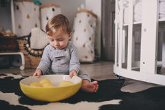 Cute happy baby boy eating cookies at home and playing with plate of lemons. Lifestyle indoor capture Stock Photo