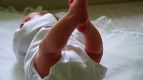 Cute happy baby boy lying and playing on a white bed stock video footage