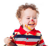 Cute happy baby boy playing with paints Royalty Free Stock Image