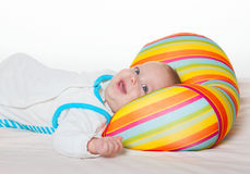 Cute happy baby with bright cushion Royalty Free Stock Images