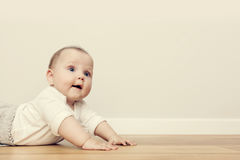 Cute happy baby crawl on wooden floor and smiling. Vintage Stock Photo