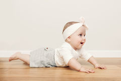 Cute happy baby crawl on wooden floor wearing funny headband Stock Image