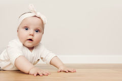 Cute happy baby crawl on wooden floor wearing funny headband Stock Photography