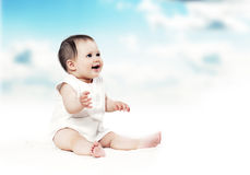 Cute happy baby on the floor on a sky background Stock Images
