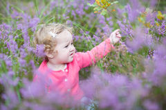 Cute happy baby girl with beautiful purple flowers Royalty Free Stock Photos