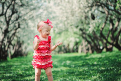 Cute happy baby girl in funny pink romper walking outdoor in spring garden Royalty Free Stock Photo