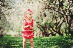 Cute happy baby girl in funny pink romper walking outdoor in spring garden Royalty Free Stock Image