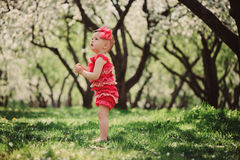 Cute happy baby girl in funny pink romper walking outdoor in spring garden Royalty Free Stock Photography