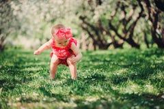 Cute happy baby girl in funny pink romper walking outdoor in spring garden Stock Photos