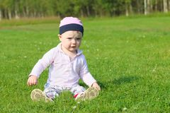 Cute happy baby girl in hat sits on green grass Stock Photo