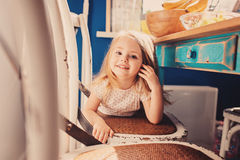 Cute happy baby girl having fun on the kitchen. In sunny morning Stock Photo