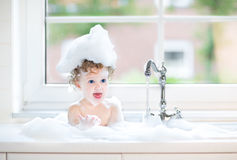 Cute happy baby girl playing with foam in kitchen sink. Cute happy baby girl with big blue eyes playing with water and foam in a kitchen sink next to a window Stock Images